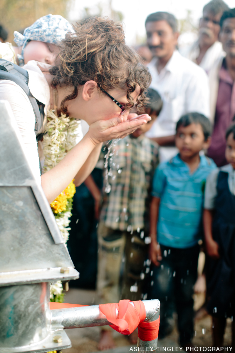 Tasting the water from the new borehole. Photo Credit: Ashley Tingley